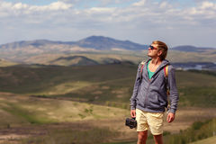 A young man with a camera in the mountains. Royalty Free Stock Images