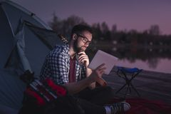 Man camping by the lake. Young man camping on the lake docks, sitting on the tent entrance and reading the news on a tablet computer stock photo