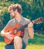 Young man camping playing guitar outdoor Royalty Free Stock Photos
