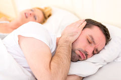 Young man can't sleep because of girlfriend's snoring Royalty Free Stock Photo