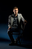 Young man with cane sitting on chair Stock Photo