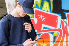 Young man in a cap with a cellphone. In his hands is picking the music royalty free stock photo