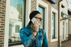 Young man in cap and sunglasses talking on smartphone and looking away Royalty Free Stock Images