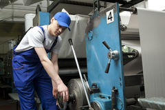 Young man in cap working on offset printing machine. In print factory royalty free stock photos
