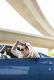 Young man in car combing hair in rear view mirror, side view Royalty Free Stock Images