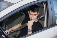 Young man in car fastening seat belt for safety. Young handsome man in car fastening seat belt for his safety stock photos