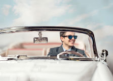 Young man in a car. Young handsome man wearing sunglasses in a car Stock Photo