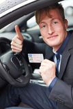 Young man in car holding drivers Royalty Free Stock Photo