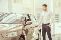 Young Man in a Car Rental Service Test Drive Concept. Young man standing near the car opening door rental service stock image