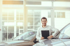 Young Man in a Car Rental Service Transportation Concept. Young man in a car rental service holding contract stock images
