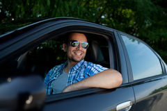Young man in car smiling. Handsome man smiling in his own car Royalty Free Stock Photography