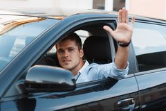 A young man in a car stuck his hand out the window. Man approves Stock Images