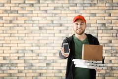 Young man with cardboard pizza boxes, paper bag and mobile phone on brick wall background. Food delivery service royalty free stock photo