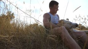 Young man caress, hugging and kissing his labrador outdoor at nature. Playing with golden retriever. Dog licking male stock video footage