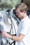 Young man caressing a horse Royalty Free Stock Image