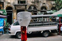 Young man caring aluminum buckets in Yangon. Young man caring aluminum buckets in Yangon, Myanmar Stock Photo