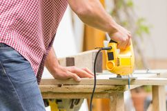 Young man carpenter working with electric jigsaw Stock Photography