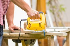Young man carpenter working with electric jigsaw Stock Photos