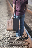 A young man carries an antique suitcase on railway. Travel Stock Photography