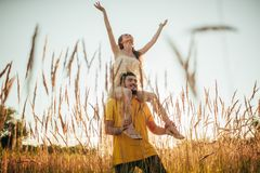 Young man carries girl on his shoulders at meadow. Young men carries girl on his shoulders at meadow on background of grass and spikes royalty free stock images