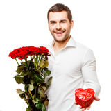Young man carries heart shaped box and flowers Stock Image