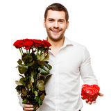 Young man carries heart shaped box and flowers Royalty Free Stock Photo