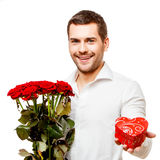 Young man carries heart shaped box and flowers Stock Photography