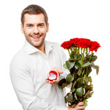 Young man carries heart shaped box and flowers Stock Images