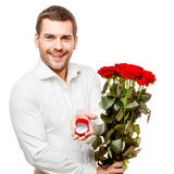 Young man carries heart shaped box and flowers Royalty Free Stock Photography