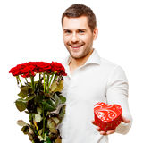 Young man carries heart shaped box and flowers Stock Photo