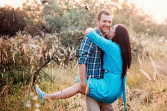 Young man carries in his arms a young attractive girl in a park Royalty Free Stock Image