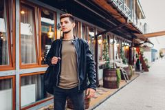 Young man carrying acoustic guitar in case while walking on city street by cafe. Hipster student of musical college royalty free stock images