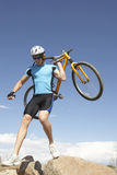 Young Man Carrying Bicycle On Rocks Stock Images