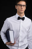 Young man carrying book on black background. Royalty Free Stock Image