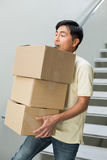 Young man carrying boxes against staircase Stock Image