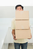 Young man carrying boxes in front of his face Royalty Free Stock Photos