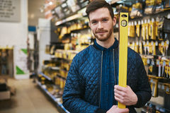 Young man carrying a builders or carpenters level Royalty Free Stock Photography
