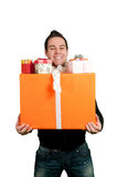 Young man carrying a bunch of presents Royalty Free Stock Images