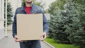 Young man carrying a cardboard box and walking outdoor.  stock video