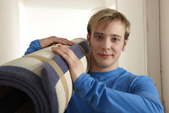 Young man carrying carpet Royalty Free Stock Photography