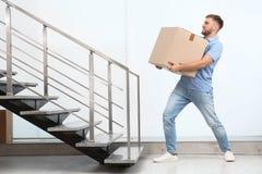 Young man carrying carton box indoors. Posture concept stock photos