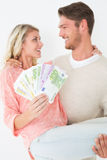 Young man carrying cheerful woman with banknotes Stock Photos