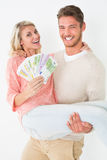 Young man carrying cheerful woman with banknotes Stock Images