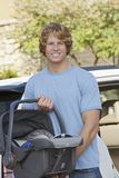 Young Man Carrying Cradle Standing By Car Royalty Free Stock Photo