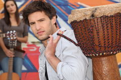 Young man carrying a djembe Royalty Free Stock Photography