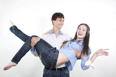 Young man carrying girlfriend in his arms Royalty Free Stock Photography