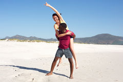 Young man carrying girlfriend on his back on beach Royalty Free Stock Photos