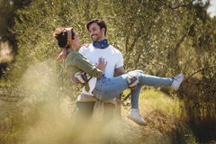 Young man carrying girlfriend by trees at farm Stock Photography