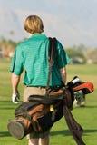 Young Man Carrying Golf Bag Stock Photography