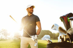 Young man carrying golf club while standing on field royalty free stock photography